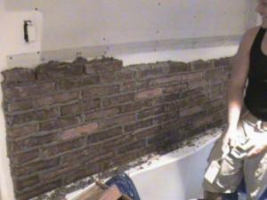 Masonry workers laying brick in bathroom.