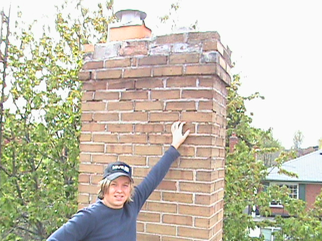 Clint Turnbull standing in front of crumbling chimney.