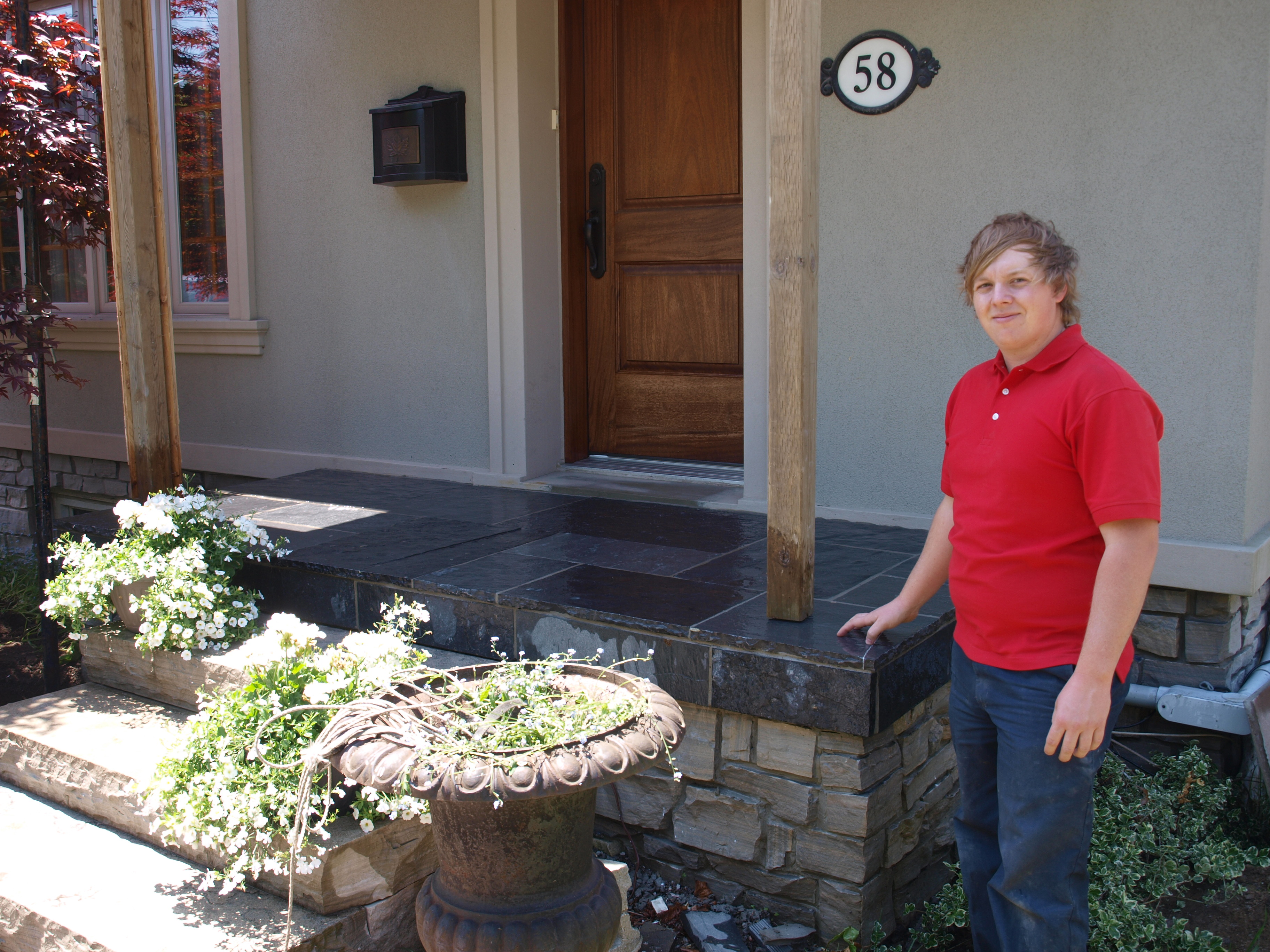 Clint Turnbull in front of newly built front porch.