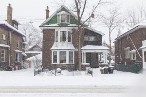 A house in Toronto during a snow storm, showing lots of snow outside the building