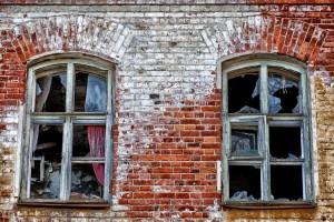 19th century brick building with broken windows.