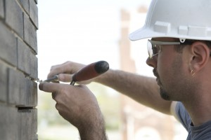 Construction mason pointing brick joints.